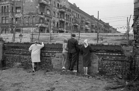 People Look Over Barb Wire at Berlin Wall